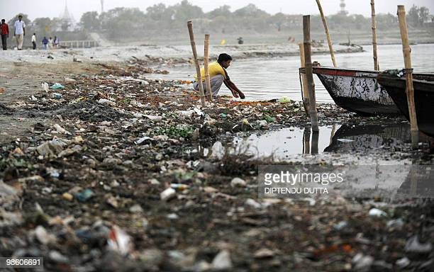 An Indian boatman sits near the polluted river waters of The Ganges at Sangam the confluence of the Ganges Yamuna and mythical Saraswati rivers in...