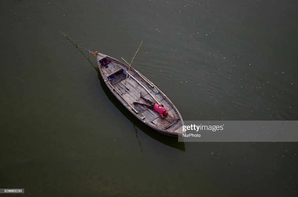 An indian boatman takes rest in his boat on Partially dried Ganges River,during a hot day in Allahabad on May 6,2016.Much of India is reeling under weekslong heat wave and severe conditions that have decimated crops, killed livestock and left atleast 330 millions indians without enough water for their daily needs.
