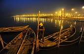 An Indian boatman ties his boat to a rope fence at Sangam during the annual Magh Mela in Allahabad on January 10 2015 The Magh Mela event lasts over...