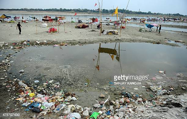 An Indian boatman walks past polluted water of the river Ganga at Sangam the confluence of the Ganges Yamuna and Saraswati rivers in Allahabad on...