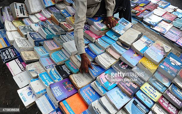 An Indian book seller arranges books for the competitive government and semigovernment services examinations at a second hand book stall on the...