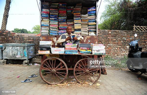 An Indian book seller waits for customers at a second hand book stall on the roadside near the university in Allahabad on June 4 2015 After...
