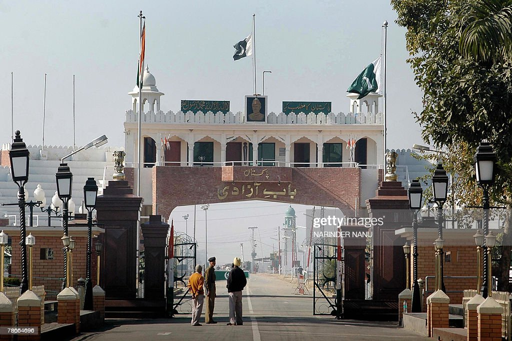 An Indian Border Security Force official (C) talks with others as they stand on the border between India and Pakistan at the Wagah Border Post, 28 December 2007, with Pakistani national flags flying at half-mast, in the wake of former Pakistani Prime Minister Benazir Bhutto's assassination. The Pakistan interior ministry said Friday there was 'every possibility' the Islamic extremist Al-Qaeda network was behind the assassination in Rawalpindi of opposition leader Benazir Bhutto. AFP PHOTO/NARINDER NANU