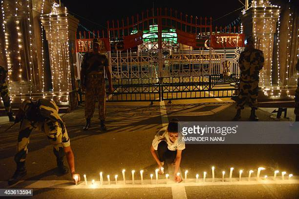An Indian Border Security Force soldier and a reveller place candles during a vigil marking the country's independence days at the IndianPakistan...
