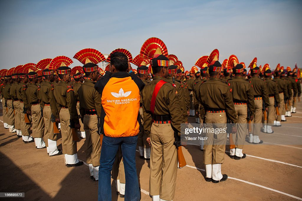 An Indian Border Security Force (BSF) soldier in civilian clothing adjusts turbans of his colleagues during their passing out parade on November 24, 2012 in Humhama, on the outskirts of Srinagar, the summer capital of Indian administered Kashmir, India. 545 new trained recruits of the Indian paramilitary Border Security Force constables took oaths during their passing out parade after successfully completing 36 weeks of basic training which involved physical fitness, weapons handling, map reading, counter-insurgency operations and human rights. The recruits will join Indian soldiers to fight militants in Kashmir, a spokesman of the paramilitary BSF said. India has already close to a million soldiers posted in Jammu and Kashmir, making the disputed Himalayan region one of the most militarized zone in the world
