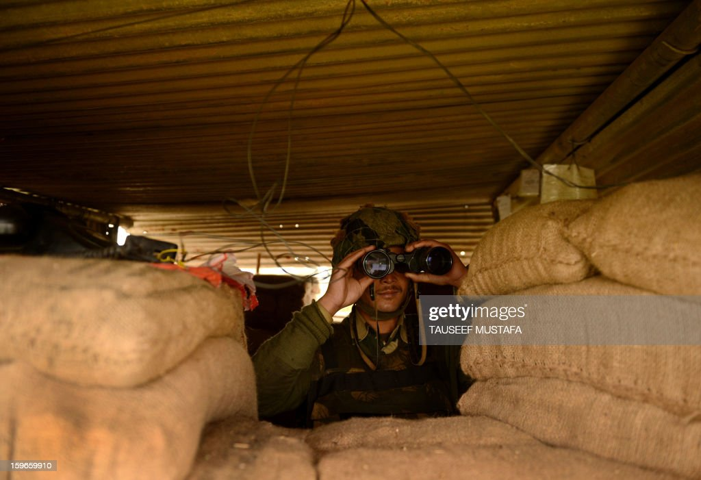 An Indian Border Security Force (BSF) soldier keeps vigil inside an outpost along the India-Pakistan border in Suchit-Garh, 36 kms southwest of Jammu on January 18, 2013. On both sides of the de facto border in Kashmir, villagers living on one of the world's most dangerous flashpoints have special reason to fear the return of tension between India and Pakistan. AFP PHOTO/Tauseef MUSTAFA