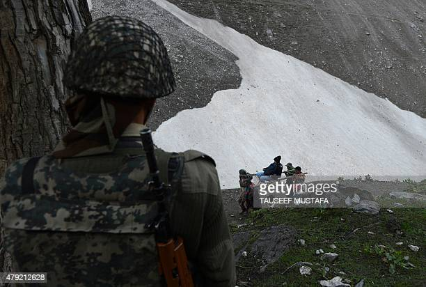 An Indian Border Security Force soldier stands guard as a Hindu devotee is carried by Kashmiri porters during the start of the annual journey from...