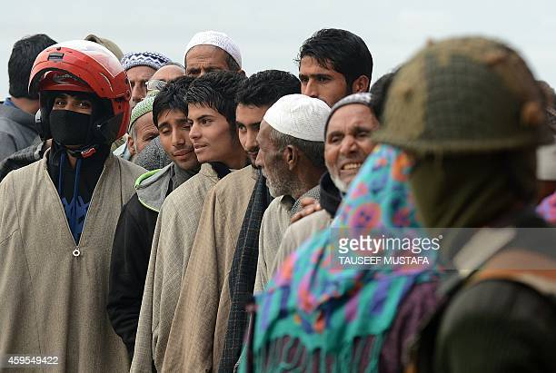 An Indian Border Security Force soldier stands guard as Kashmiri muslim voters queue outside a polling station at Manasbal about 20 kms from the...