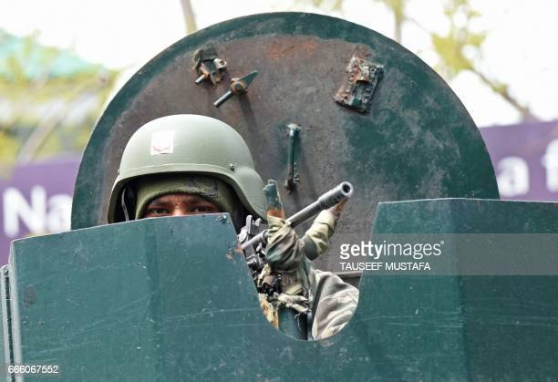 An Indian Border Security Force soldier stands guard on top of an armoured vehicle outside a polling station in Srinagar on April 8 2017 The Kashmir...