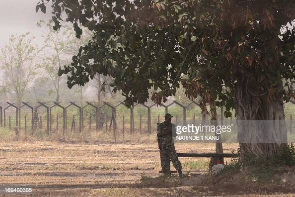 An Indian Border Security Force soldier stands in the shade of a tree during hot weather along the India–Pakistan border in Wagah some 35kms from...