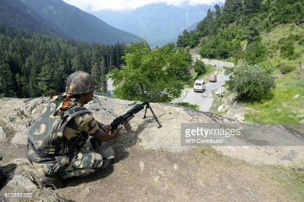 An Indian Border Security Force soldier surveys the area on top of a hill in Chandanwari in Anantnag district some 115 km southeast of Srinagar...