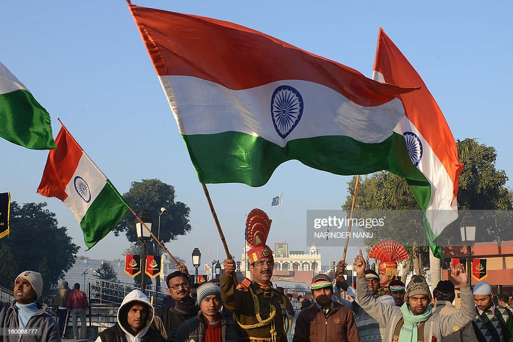 An Indian Border Security Force (BSF) soldier waves his national flag as he celebrates the country's 64th Republic Day at the India-Pakistan border post in Wagah on January 26, 2013. India celebrated its 64th Republic Day with a military parade in several towns across the country. AFP PHOTO/NARINDER NANU