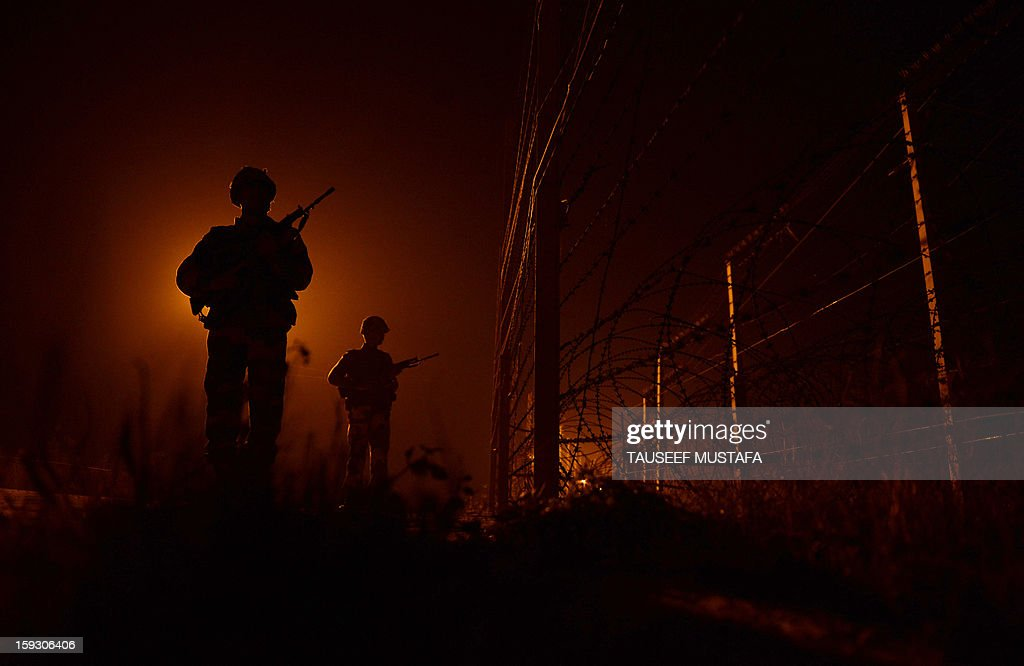 An Indian Border Security Force (BSF) soldiers patrols along the border fence at an outpost along the India-Pakistan border in Suchit-Garh, 36 kms southwest of Jammu on January 11, 2013. Pakistan summoned the Indian ambassador to protest against 'unacceptable and unprovoked' attacks by the Indian army that killed two Pakistani soldiers in five days in Kashmir. AFP PHOTO/ Tauseef MUSTAFA