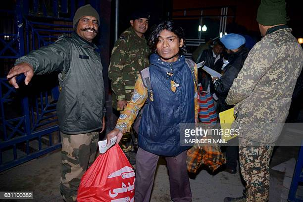 An Indian Border Security Forces gestures as an Indian fisherman crosses the IndiaPakistan border at Wagah some 35kms west of Amritsar on January 6...