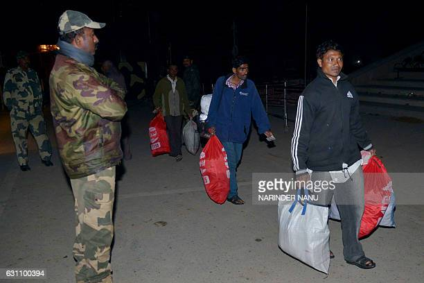An Indian Border Security Forces stands as Indian fishermen cross the IndiaPakistan border at Wagah some 35kms west of Amritsar on January 6 after...