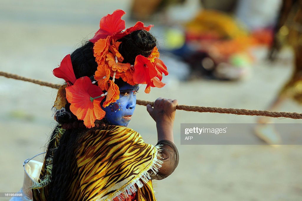 An Indian boy dressed as Lord Shiva watches during the Kumbh Mela festival in Allahabad on February 18, 2013. The Kumbh Mela in the town of Allahabad will see up to 100 million worshippers gather over 55 days to take a ritual bath in the holy waters, believed to cleanse sins and bestow blessings.