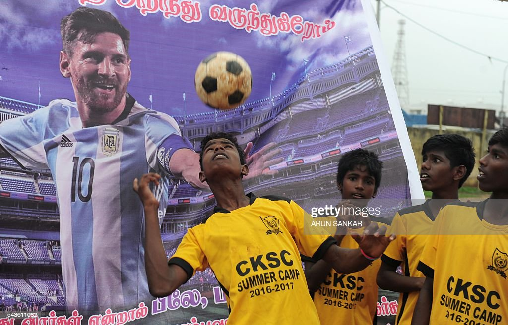 An Indian boy heads a football in front of a poster of Argentinian footballer, Lionel Messi displayed at a football ground and saying that Messi should come back, in Chennai on June 29, 2016. Argentina was defeated in the Copa America final against Chile, 4-2, in a penalty shoot-out. Argentinians begged Lionel Messi - who tearfully decided to quit the international team after missing a spot-kick in the shootout - not to leave the national team despite its traumatic final. / AFP / ARUN