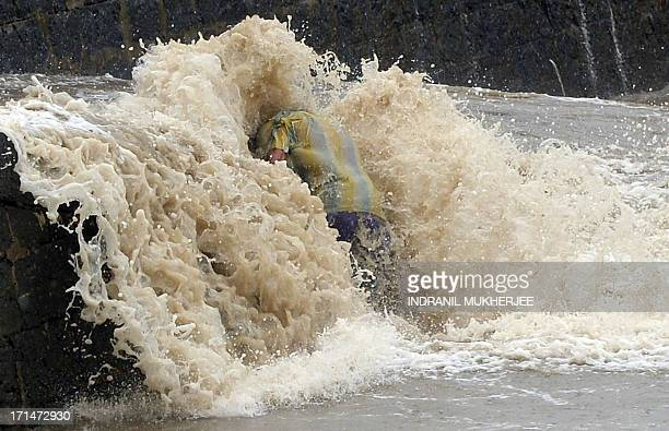 An Indian boy holds on as waves lash the retaining wall of the iconic Gateway of India off the Arabian sea in Mumbai on June 25 2013 The monsoon...