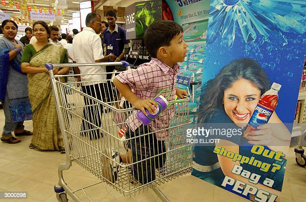 An Indian boy kneels in a shopping trolley next to a Pepsi advertising stand featuring actress Kareena Kapoor who inaugurated the opening of GIANT...