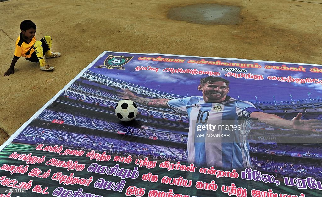 An Indian boy sits next to a poster of Argentinian footballer, Lionel Messi displayed at a football ground and saying that Messi should come back, in Chennai on June 29, 2016. Argentina was defeated in the Copa America final against Chile, 4-2, in a penalty shoot-out. Argentinians begged Lionel Messi - who tearfully decided to quit the international team after missing a spot-kick in the shootout - not to leave the national team despite its traumatic final. / AFP / ARUN