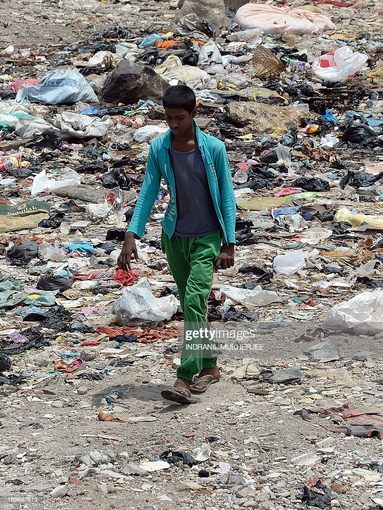 An Indian boy walks across an open space strewn with garbage adjoining a slum in Mumbai on June 4, 2013 on the eve of World Environment Day. India's cities are becoming more polluted and unhealthy, according to a new survey published Monday showing growing concern about the impact of high economic growth on the environment. The Energy and Resources Institute (TERI) research group based in New Delhi questioned 4,039 people living in India's six biggest cities about their perceptions, opinions and awareness of the environment and green issues over the last five years. AFP PHOTO/ Indranil MUKHERJEE