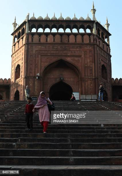 An Indian boy walks down the stairs of the Jama Masjid with her mother on her way to school in the old quarters of New Delhi on February 27 2017 /...