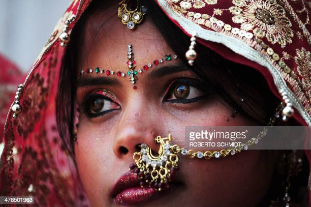 An Indian bride looks on as she and ten other women waiting to marry wait for their grooms to arrive at their wedding ceremony at a local Hindu...