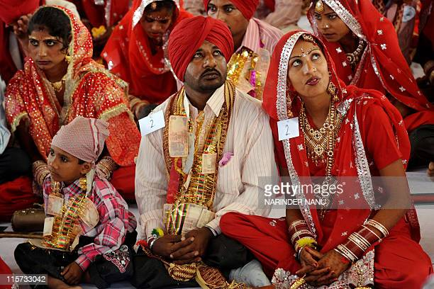 An Indian bride sits with her groom during a mass marriage ceremony for some 187 lowincome couples from the IndiaPakistan border area at Gurdwara...