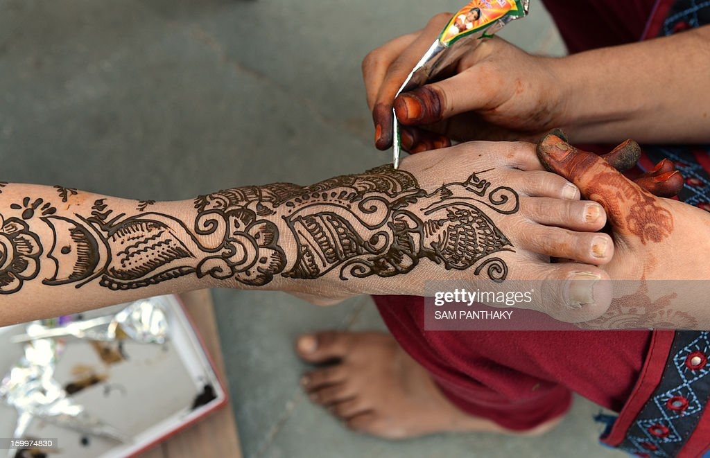 An Indian bride that is visually impaired has henna applied to her legs by a group of volunteers from the Andh Kanya Prakash Gruh (AKPG) institute as a part of ritual ahead of her marriage in Ahmedabad on January 24, 2013. Ten visually impaired women are scheduled to participate in a mass wedding at the institute on January 27. AFP PHOTO / Sam PANTHAKY
