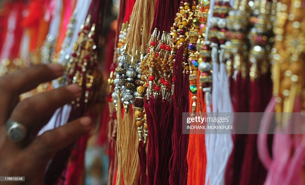 An Indian browses through 'rakhis' (sacred thread) on display at a market ahead of the Hindu festival of Raksha Bandhan in Mumbai on August 19, 2013. The annual Hindu festival of Raksha Bandhan, which commemorates the abiding ties between siblings of opposite sex, is marked by a very simple ceremony in which a woman ties a rakhi, which may be a colorful thread, a simple bracelet, or a decorative string, around the wrist of her brother. This year's Raksha Bandhan will be celebrated across India on August 20. AFP PHOTO/Indranil MUKHERJEE
