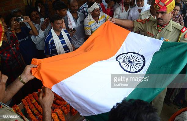 An indian BSF Solider covers the cofffin of Martyr Girish Shukla with Tri color flag to pay respect before a last ride in his Home village Sulmai 41...