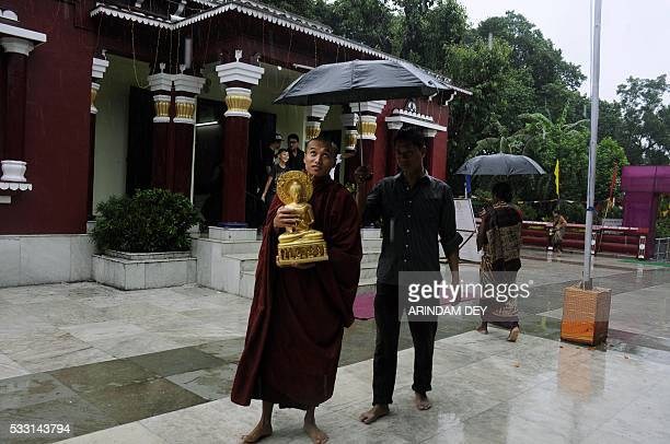 An Indian Buddhist Monk is shielded from rain as he carries an idol during a prayer ceremony for the 2560th birth anniversary of the birth of Buddha...