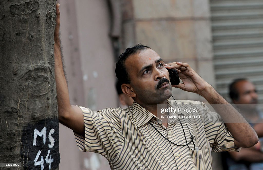 An Indian bystander makes a telephone call while watching share prices on the digital broadcast on the facade of the Bombay Stock Exchange (BSE) in Mumbai on October 4, 2012. In early afternoon trading on the Bombay Stock Exchange, stocks were at a 15-month high, up 1.06 percent at 19,069.56 points, while the rupee strengthened to its strongest in five-and-a-half months at 51.79 dollars.