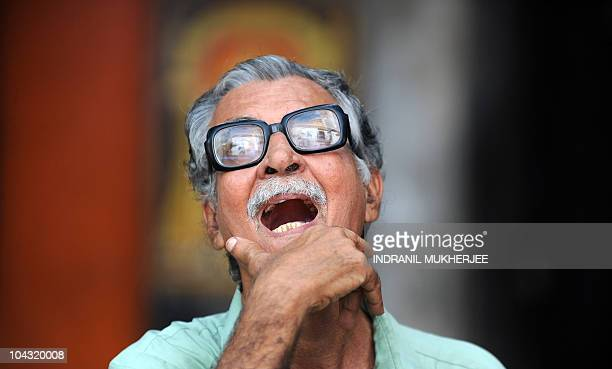 An Indian bystander reacts while watching the Sensex index on the digital broadcast on the facade of the Bombay Stock Exchange in Mumbai on September...