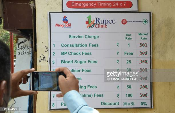 An Indian bystander takes photographs of a board detailing treatment charges outside a 'One Rupee Clinic' emergency medical room in Mumbai on May 10...