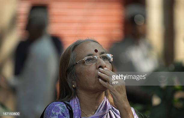 An Indian bystander watches share prices on the digital broadcast on the facade of the Bombay Stock Exchange in Mumbai on November 29 2012 Asian...