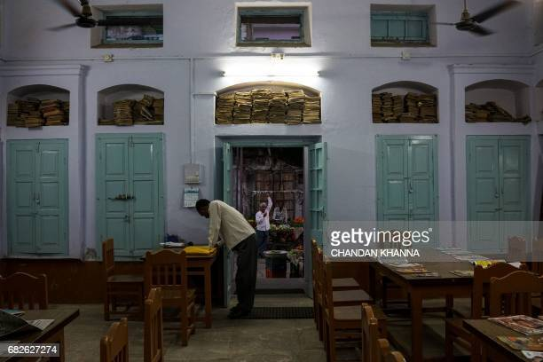 An Indian caretaker of a public library works in Kekri some 78 kms south of Ajmer on May 13 in the northern state of Rajasthan / AFP PHOTO / CHANDAN...