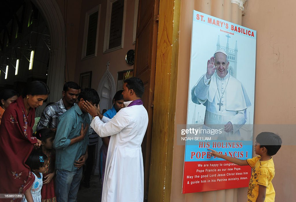 An Indian Catholic priest blesses devotees after mass as a young boy touches a poster of Pope Francis at Saint Mary's Basilica in Secunderabad the twin city of Hyderabad on March 17, 2013. The son of an Italian emigrant railway worker, Francis is a moderate conservative who is unlikely to change key doctrine but experts say that he could push for more social justice and a friendlier faith. AFP PHOTO / Noah SEELAM