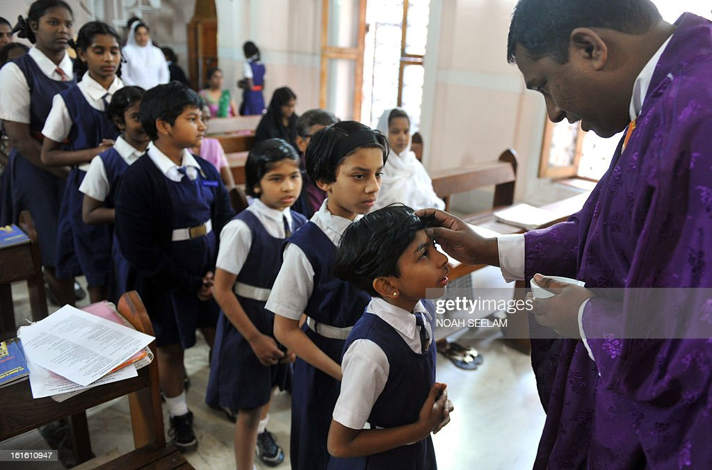 An Indian Catholic Priest marks the symbol of the cross with ash on the forehead of a young Christian devotee during an Ash Wednesday service at Saint Mary's Basilica in Secunderabad, the twin city of Hyderabad, on February 13, 2013. Catholics began the 40 day Lenten season, by observing observe Ash Wednesday, which culminates in Holy Week. AFP PHOTO / Noah SEELAM