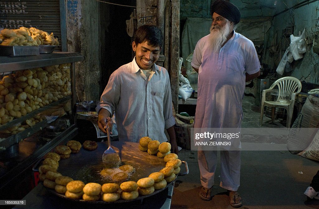 An Indian 'chaat' - savoury snack - vendor fries potato patties on a stall at a market in New Delhi on April 4, 2013. India's premier Manmohan Singh on Wednesday said the country's economy could return to high growth rates as he urged the nation's top industrialists to 'keep the faith'. AFP PHOTO/ Anna ZIEMINSKI