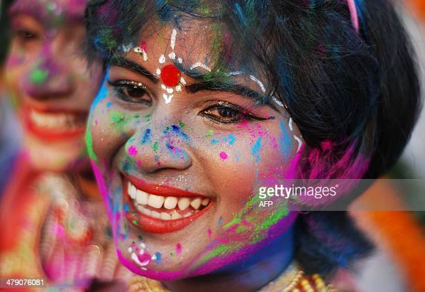 An Indian child adorned with coloured powder takes part in celebrations for the spring festival Holi in Bhubaneswar on March 16 2014 Holi the popular...