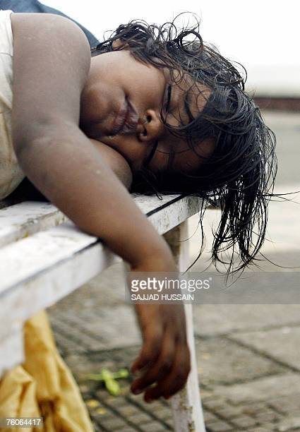 An Indian child beggar sleeps on a bench at Worli Sea Face in Mumbai 12 August 2007 Though India has shown a remarakable growth in its economy with...