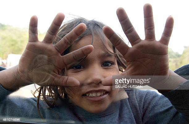 An Indian child begger places her hands on the car window as she begs for alms on the streets of New Delhi on January 6 2015 India has been stuck in...