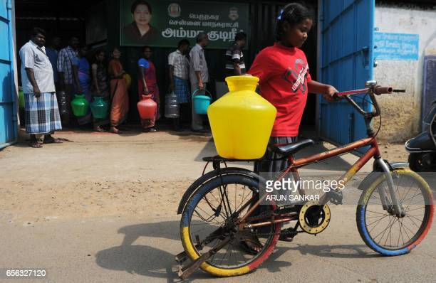 An Indian child carries a plastic container full of purified drinking water on a bicycle after collection from a government distribution centre in...