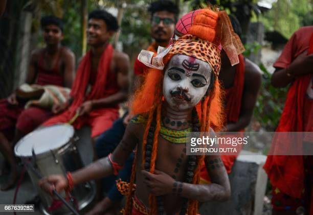 TOPSHOT An Indian child dressed as the Hindu deity Shiva dances with others as they begs for alms in Siliguri on April 12 ahead of the 'Charak'...