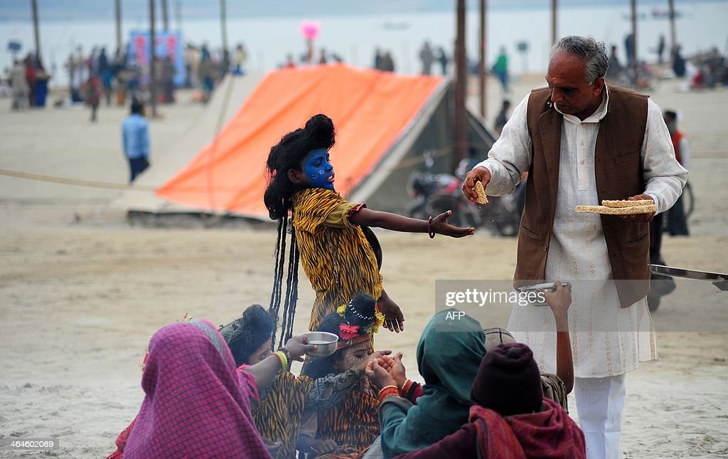 An Indian child dressed as the Hindu god Shiva receives sweetmeats from a devotee at Sangam during the Magh Mela Festival in Allahabad on January 23...