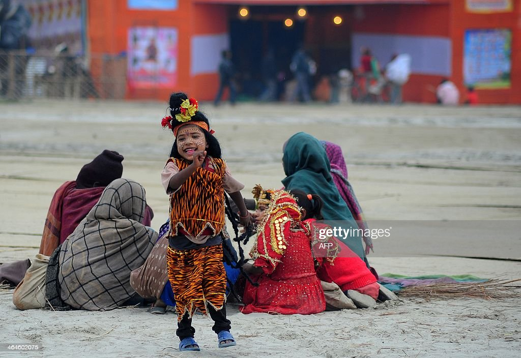 An Indian child dressed as the Hindu god Shiva runs to collect money from devotees at Sangam during the Magh Mela Festival in Allahabad on January 23...