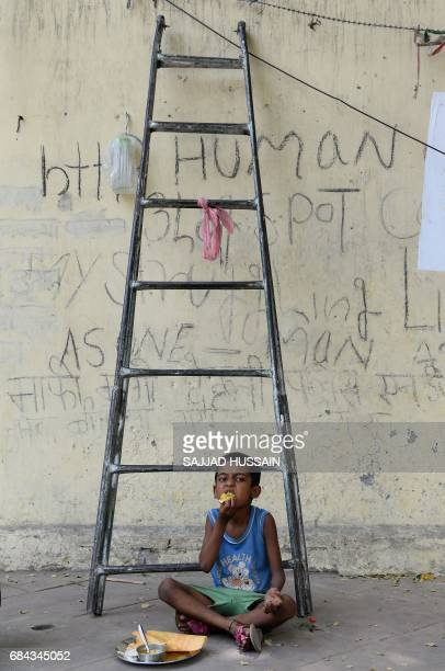 An Indian child eats food on a foothpath in New Delhi on May 17 2017 / AFP PHOTO / SAJJAD HUSSAIN