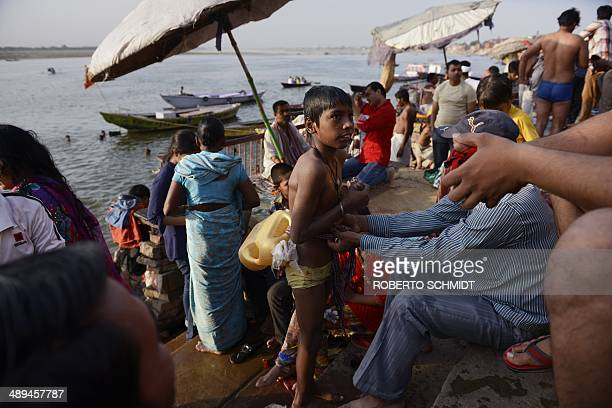 An Indian child has a plastic container attached to his torso to help him float on the water by his father as he and his family bathe on the River...