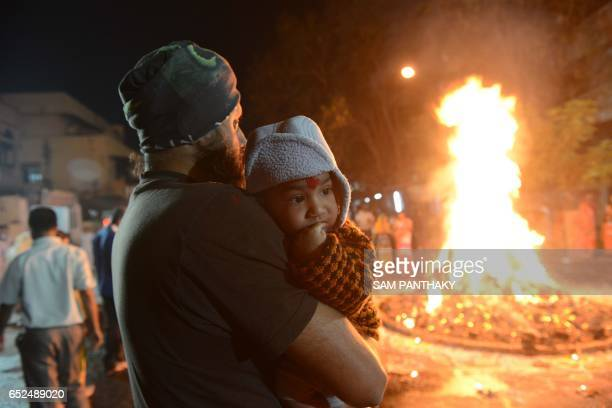 An Indian child is held next to a burning traditional 'Holika' made out of cakes of cow dung and coconuts in Ahmedabad on March 12 2017 Holika...